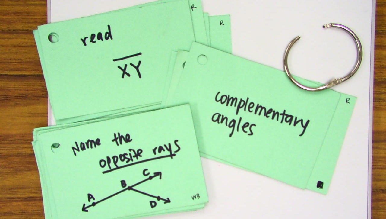 "image showing some flashcards in a pile. One has an angle and reads ""name the opposite rays"". Second reads ""complementary angles"" and third reads ""read XY bar""."